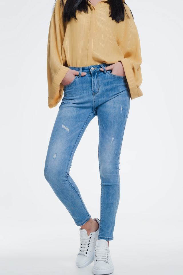 Light denim skinny jeans slight wear detail