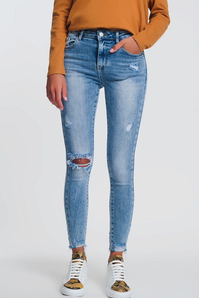 High rise super skinny jeans in light denim with one knee rip and raw hem